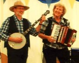Keith on banjo and Dei on accordion in a marquee at an 'American' themed corporate event in Windsor.